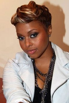 This is a classy and chic look as Chrisette Michele has her hair short all around. At the sides and back, the hair has been layered and cut very close to the head. On the top, the hair is longer and built up high. This fashionable look is great both for the home or office.Chrisette's haircut is short.The hair is coloured a dark brown with blonde highlights.
