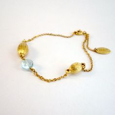 A beautiful 22ct gold-plated chain bracelet with textured bead, teardrop bead and oval blue topaz faceted gemstone. One size (adjustable).