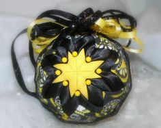 This ornament has bright yellow fabric with black satin fabric and then accented with a black, yellow and white paisley fabric
