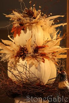 Tall white pumpkin topiary display with natural elements such as acorns and indian corn. Full tutorial.