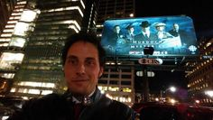 Jonny Harris (George Crabtree) standing in front of a Murdoch Mysteries billboard