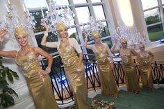 Chandelier Girls! These ladies dressed in gold shimmer and adorned with chandelier headdresses welcome guests to a reception.