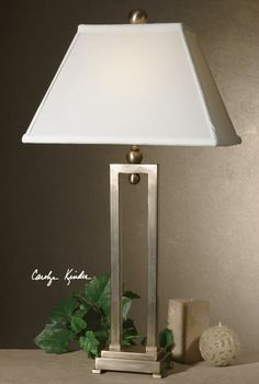 Conrad lamp -This contemporary lamp has a silver plate body with a hand applied antiqued stain. The hand sewn fabric shade is a rectangle bell.