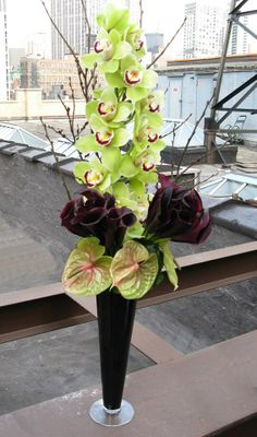 This beautiful, tall arrangement consists of green Cymbidium Orchids, plum Calla Lilies, and green Anthurium blooms.