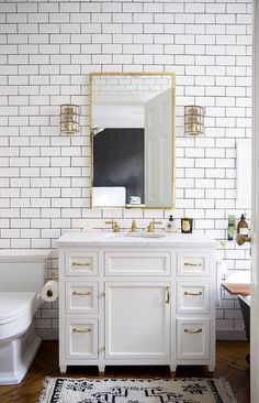 Bathroom with white subway tile, brass hardware and Persian rug