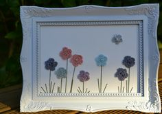 Here's a little mixed media crochet flower 'painting' Ive been working on. It's made using the same basic flower found here, but the leaves and stalks are each sewn with a single long stitch... an...
