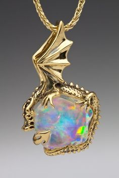 AURORA DRAGON PENDANT 18K Gold, Aurora Dragon, clutches an 11.5 carat Mexican Fire Opal. This icy, ethereal stone shimmers with all the colors of the rainbow. Aurora Dragon is 1 1/2 inches high and 1 inch across.