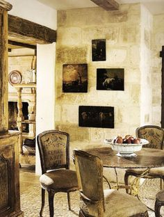 Aged plaster on the wall offsets the art on this lovely french home's wall.