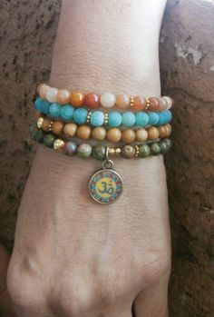 I love the styling of these 4 mala bracelets.  I would make one tiger's eye w/ an ohm charm, one sandalwood w/ a  turquoise feature, one jade w/ a lotus bead & one w/ a buddah charm!