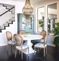 Well designed cottage dining room is illuminated by an Arteriors Maxim Chandelier hung over a whitewashed pedestal dining table surrounded by gray cane back dining chairs accented with blue floral seat cushions.