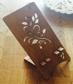Laser Cut Mobile Phone Stand.  Our beautiful, nature inspired phone stand is cut from a sustainable poplar wood base with oak stain finish.  The stand is a generic size and is ideal for most modern smartphones.  The design allows for the phone charger cable to be plugged in whilst the phone is on the stand making perfect for overnight charging on a bedside table. J&J