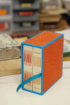 orange and blue long stitch books in a case