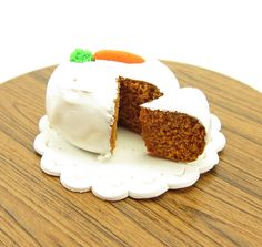 """This dollhouse size one inch scale carrot cake is made from polymer clay and has white cream cheese frosting and a """"fondant"""" carrot on top. There is a slice cut to reveal the moist carrot cake inside."""