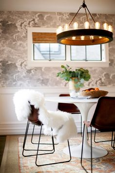 A modern and industrial dining space with cloudy wallpaper and oranges on the table