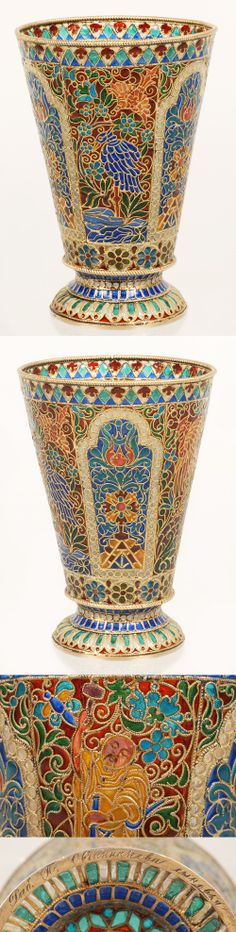 A large Russian gilded silver and plique-a-jour enamel beaker, made by Pavel Ovchinnikov, Moscow, circa 1895. Of tapering cylindrical form, the body decorated with panels depicting flower heads and foliage ahainst a blue ground within white beaded borders, between scenes of brightly colored tropical birds and a man with a mustache dressed in yellow robes, the twisted cable rims, on a domed circular foot with a brightly colored band within beadedborders