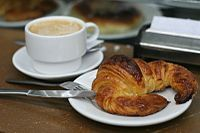 A typical Italian breakfast, consisting of cappuccino and brioche / croissant.  The first Italian meal is breakfast, or colazione. Traditional Italian breakfasts are continental-style, similar to those of France, Greece, Portugal or Spain. The traditional breakfast in Italy is simply Caffè e latte (hot coffee with milk) or coffee with bread or rolls, butter, and jam—known as prima colazione or just colazione.