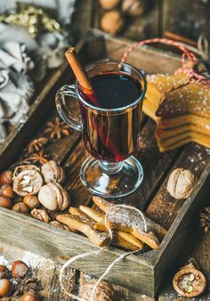Glass of mulled wine gingerbread cookies spices in wooden tray by 2enroute