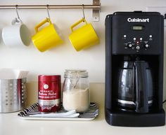 Hang a towel bar with shower curtain hooks for coffee mugs in the kitchen. Great for small spaces!