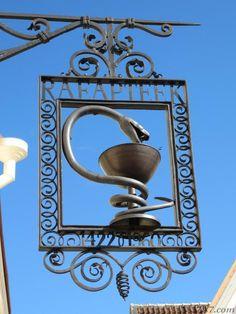 Symbol of medicine - a snake - on Town Hall pharmacy sign in Tallinn, Estonia