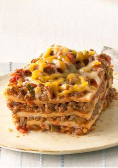 Our Favorite Mexican-Style Lasagna -- Create a little fusion with ooey-gooey cheese, beans and taco beef layered up and baked like lasagna in this tasty recipe.