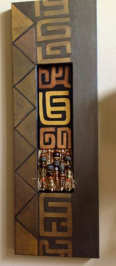 Shadow box canvas with inset Kuba patterned canvas accented with raffia and beads from Ghana