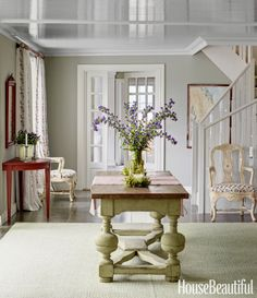 A 17th-century table anchors the entry of a Swedish summer house, and its color is echoed in the custom Shyam Ahuja rug. The walls are painted in a matte finish, but the ceiling is high gloss, to bounce more light into the room. Click through for more foyer decorating ideas.