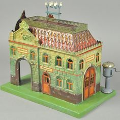 "Marklin Central Train Station.  Germany, Railway Station #2041, gauge '1', circa 1898-1906, hand painted tin, nicely embossed building, very colorful overall, interior features benches and ticket office, telegraph poles at roof, bell stand on base, opening doors. 8 1/4"" x 13 1/2"" w."