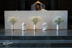 ołtarz udekorowany bukietami z gipsówki i lampionami