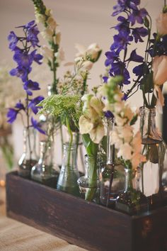 Love the combination of purple and ivory! Glass bottles of delphinium and Queen Anne's lace in a wooden trough make an eye-catching centerpiece! {@bitofivory}