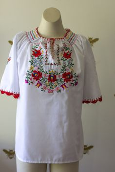 Bohemian Traders Folk Blouse is intricately constructed and full of ingenious colour combinations. Hand crafted in Hungary using traditional European Folk techniques on 100% cotton. We adore this easy fitting blouse's bright  embroidery