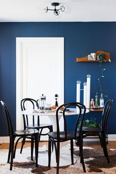 living room + dining room makeover reveal. boho meets modern styling. marble dining table, navy blue pop wall paint color, black bentwood thonet chairs, metallic cowhide rug, vintage bar cart.
