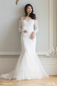 An off the shoulder sweetheart neckline 'fit and swish' gown with train. Look out for the long sleeves and the lace illusion back with covered buttons and loops.