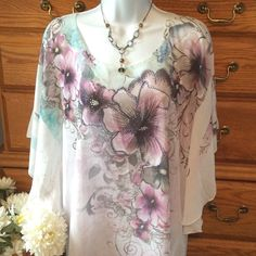"Studio Gem Sheer Poncho Top NWT 100% polyester.  Approximately 34"" in length.  Pretty floral and some bling.  Sheer chiffon feel.  Brand new.  When measured flat from armpit to armpit it is 24"" across but then it's swings out.    Very light weight. Studio Gem Tops Tunics"