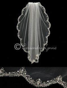 A scrolling silver embroidered design enhances the edge of this scalloped bridal veil. Each point has a single teardrop rhinestones while silver lined seed bead
