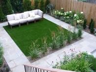 This pretty white and green outdoor space utilizes artificial turf for a low-maintenance lawn.