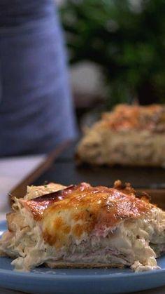Receita com instruções em vídeo: Torta cremosa de pão de forma, ideal para dividir com a galera! Ingredientes: 2 colheres de sopa de azeite de oliva, 1 cebola cortada em cubos, 1 dente de alho picado, 1kg de frango cozido e desfiado, 1 xícara de molho branco, 2 xícaras de requeijão cremoso, Sal a gosto, Pimenta do reino a gosto, 1 pitada de orégano, 1 pacote de pao de torta fria, 200g de presunto, 200g de queijo muçarela ralado