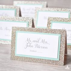 Tented, three layer escort card features a base of glitter paper and accent layer of coal matte card stock. Top layer is printed on matte white card stock in silver ink with a pink border.