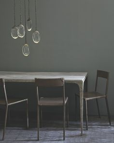 Group of Celestial Pendants hang over Whippet Table and Sable Chairs by Ochre | Remodelista