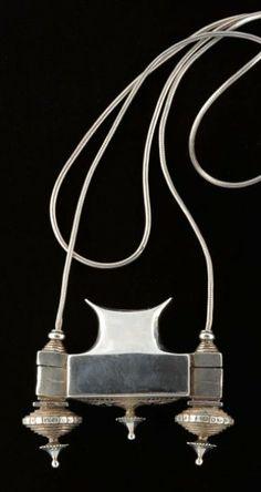 Reliquaire avec collier Reliquaire en argent de forme très structurée, soutenu par une chaîne à mailles ?queue de rat'. Le corps du reliquaire s'ouvre en deux parties. La base inférieure présente des motifs ciselés représentant des oiseaux. Argent Inde du sud
