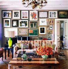 An eclectic living space with large gallery wall, colorful sofa, and orange floral arrangement on coffee table