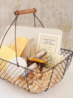 DIY Food Gift: Line a vintage basket with decorative packing material and fill with a slate cheese board, artisanal cheeses, chutney, almonds, gourmet crackers and spreading knives.