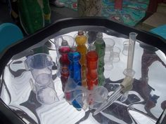 "Coloured water for pouring & measuring on a reflective sheet in the tuff spot, at Childminding Watford Playful Minds ("",)"