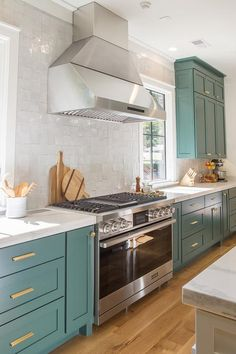 Benjamin Moor Tarrytown Green shaker cabinets stand out against white quartz countertops and white glazed backsplash cooktop tiles sans grout.