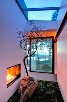 Das stille Grundstück auf Orcas Island im San Juan County in Washington wäre eine zauberhafte Filmkulisse. Für gemütliche Stunden bei Dämmerung mit Blick durch die große Fensterfront in den nebligen Wald sorgt Architekt Gary Gladwish mit einem Kaminfeuer inmitten eines lichten Wohnzimmers.