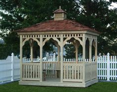 Rectangular wood gazebo surrounded by a white picket fence. The gazebo roof has cedar shake shingles and a cupola.
