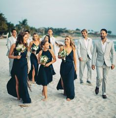 Beach wedding bridesmaids in navy blue dresses and groomsmen in grey suits