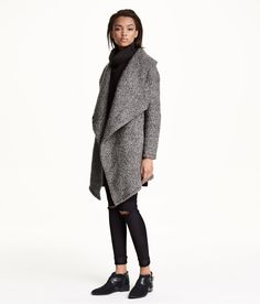Double-breasted coat in marled wool-blend bouclé yarn with a wide shawl collar, concealed press-studs at the front, side pockets and one inner pocket. Asymmetric hem and tab at the back. Lined. 50% wool, 50% polyester. Dry-clean only Art.No. 34-5281
