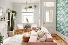 Living room with green wallpaper and pink sofa
