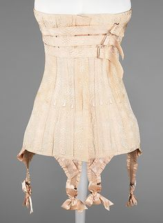"Corset: ca. 1912, American (probably), silk/bone/metal/elastic. Marking: Stamped on garter buckles: ""Velvet Grip"""