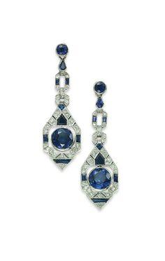 A PAIR OF ART DECO SAPPHIRE & DIAMOND EAR PENDANTS Each suspending a circular-cut sapphire collet in a sapphire & diamond geometrical openwork surround, to the similar links & circular-cut sapphire collet tops, ca 1925.